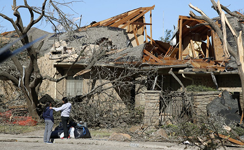 Women stand outside a house damaged by a tornado in the Preston Hollow section of Dallas