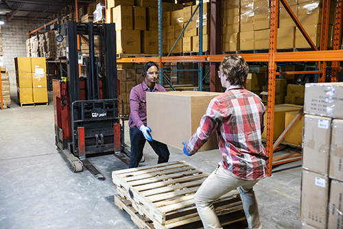 Two warehouse workers preparing to lift heavy box